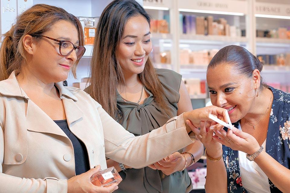 Vrouwen die parfum ruiken in een winkel